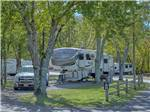 View larger image of A fifth wheel trailer parked under trees at CLABOUGHS CAMPGROUND image #5
