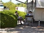 View larger image of Campers relaxing next to their RV at AMERICAN RV RESORT image #2