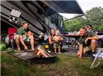 View larger image of A family sitting around a campfire at CHERRY HILL PARK image #1