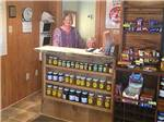 View larger image of Two staff workers behind a shelf full of jars of honey at PECAN GROVE RV PARK image #6