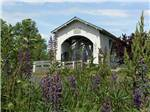 View larger image of Purple flowers in foreground of wooden bridge over creek at THE BLUE OX RV PARK image #6
