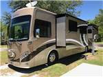 View larger image of A class A motorhome parked in a grassy RV site at FLAMINGO LAKE RV RESORT image #8