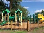 View larger image of Brightly colored plastic playground with wood chip ground and fence surrounding it at CAHOKIA RV PARQUE image #3