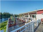 View larger image of RVs in gravel sites with trees at RIVERS EDGE RV PARK  CAMPGROUND image #9