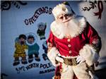 View larger image of Santa Claus posing along white fence with sunglasses at SANTA CLAUS HOUSE image #5