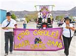 View larger image of A couple holding up a Mardi Gras sign at WAGON WEST RV PARK image #5