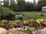 View larger image of Flowerbed with stream and picnic area at BAYFIELD RIVERSIDE RV PARK image #8
