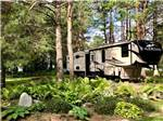 View larger image of A fifth wheel RV parked in a wooded RV site at PETOSKEY KOA image #7