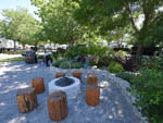 View larger image of Fire pit with log seating at VICTORIAN RV PARK image #4