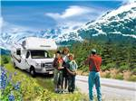 View larger image of Man taking photos of family in front of RV with mountains in background at ANCHORAGE SHIP CREEK RV PARK image #12