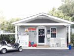 View larger image of Three people sitting on rocking chairs in front of the office at CREEKSIDE RV PARK image #11
