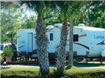 View larger image of A travel trailer parked by the water at OAK SPRINGS RV RESORT image #4