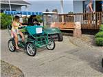 View larger image of Two kids riding a surrey on a path at OSPREY POINT RV RESORT image #7