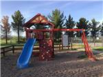 View larger image of Brightly colored red and blue playground with climbing wall and swing set at LOST ALASKAN RV PARK image #2