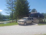 View larger image of SUV and big rig in gravel site at SPRING LAKE RV RESORT image #8
