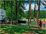 View larger image of People talking on the grass near an RV site at LAKE RUDOLPH CAMPGROUND  RV RESORT image #2