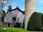 View larger image of Original barn with flag on it next to a silo at CREEKWOOD FARM RV PARK image #3
