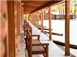 View larger image of A row of wooden benches under an awning at THE LONGHORN RANCH LODGE AND RV RESORT image #3
