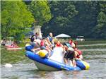 View larger image of Kids playing in the water on large floating play toy at AUSTIN LAKE RV PARK  CABINS image #6