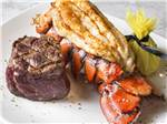 View larger image of A plate of steak and lobster at COUSHATTA LUXURY RV RESORT AT RED SHOES PARK image #6