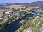 View larger image of Aerial view of park and bridge over the river at RISING RIVER RV PARK image #2