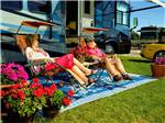 View larger image of Couple camping in RV at WHISPER CREEK RV RESORT image #1
